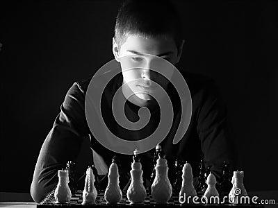 Teenage boy looking at the chessboard