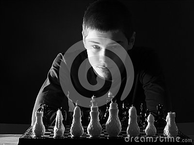 Teenage boy looking at the chessboard