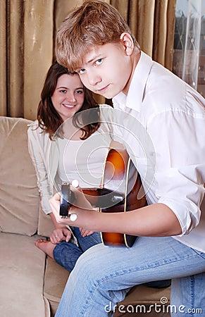 Teenage boy playing by guitar