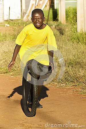 Teenage Boy Playing with Tyre - Yellow T-Shirt