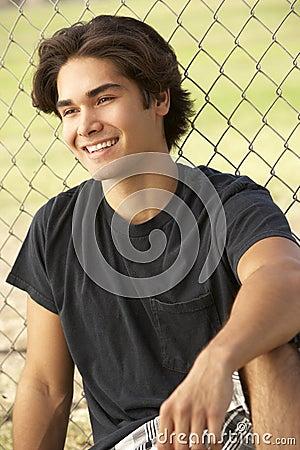 Teenage Boy Sitting In Playground