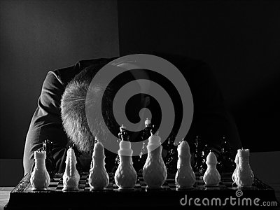 Teenage boy slumped over the chessboard