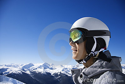 Teenage boy snowboarder in mountains.