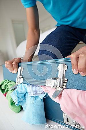 Teenage boy struggling to close full suitcase