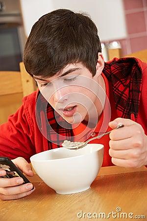 Teenage Boy Texting Whilst Eating Breakfast
