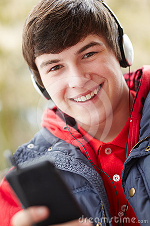 Teenage Boy Wearing Earphones Listening To Music