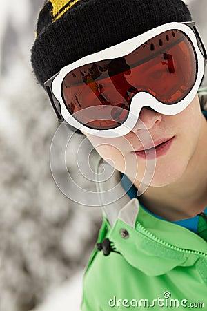 Teenage Boy Wearing Ski Goggles On Ski Holiday