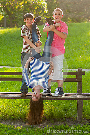 Teenage boys holding their girl friend upside down