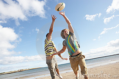 Teenage Boys Playing Rugby On Beach
