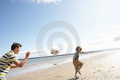 Teenage Boys Playing Rugby On Beach Together