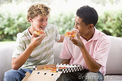 Teenage Boys Sitting On Couch Eating Pizza