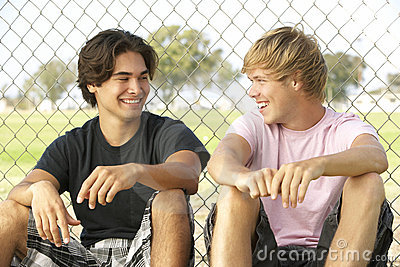 Teenage Boys Sitting In Playground