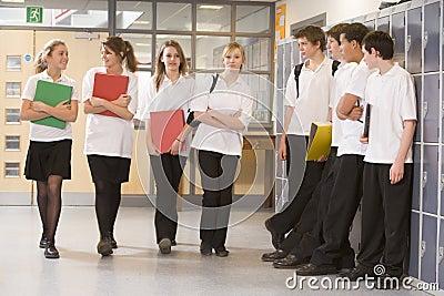 Teenage boys watching girls walk down corridor