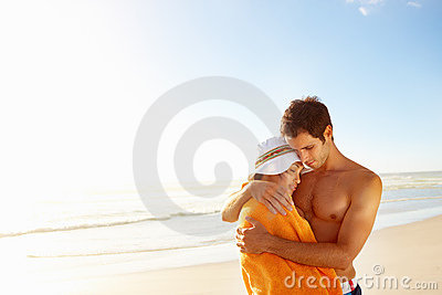 A teenage couple embracing eachother at the beach