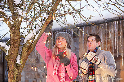 Teenage Couple Hanging Fairy Lights In Tree