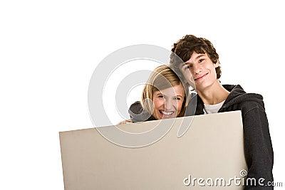 Teenage couple holding board banner