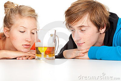 Teenage couple leaning on table with beer