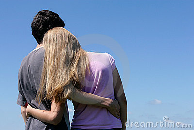Teenage couple looking at blue sky
