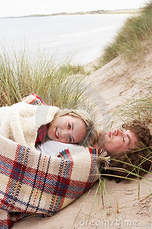 Teenage Couple Lying In Sand Dunes