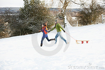 Teenage Couple Pulling Sledge Across Snowy Field