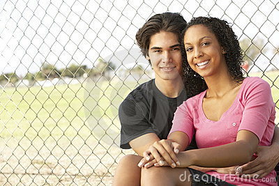 Teenage Couple Sitting In Playground