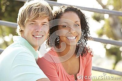 Teenage Couple Sitting In Playground