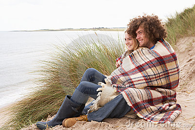 Teenage Couple Sitting In Sand Dunes