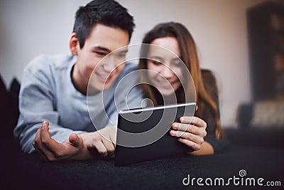 Teenage couple using digital tablet - Indoors
