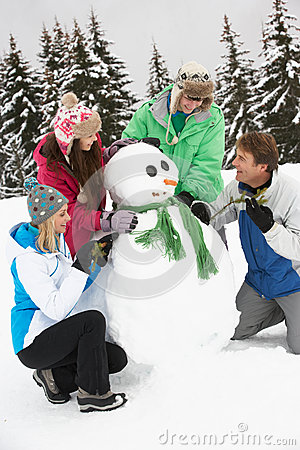 Teenage Family Building Snowman On Ski Holiday