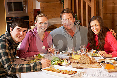 Teenage Family Enjoying Meal In Alpine Chalet