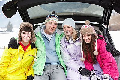 Teenage Family Sitting In Boot Of Car