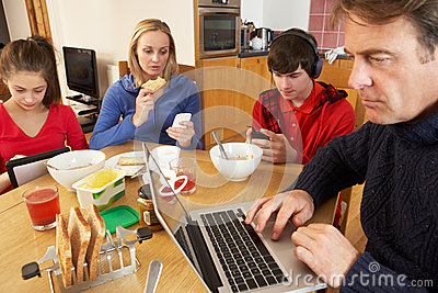 Teenage Family Using Gadgets Whilst Eating