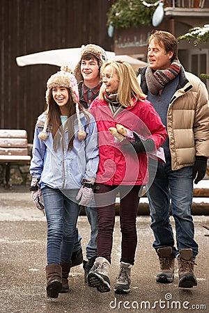Teenage Family Walking Along Snowy Town Street
