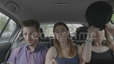 Teenage friends sitting on passenger seat inside taxi uber car enjoying the ride through town chatting and laughing together. Three teenage friends sitting on stock video