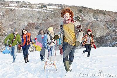 Teenage Friends Sledging In Snowy Landscape