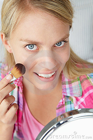 Teenage girl applying make-up
