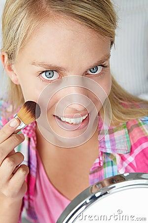 Teenage girl applying make-up