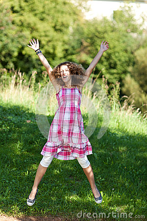 Teenage Girl With Arms Raised Jumping In Nature