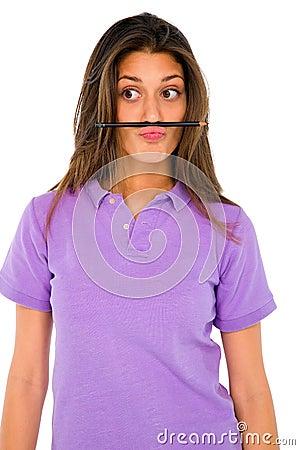 Teenage girl balancing pencil on her lip