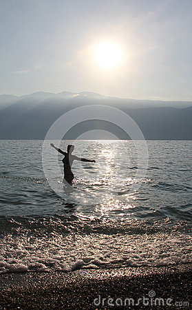 Teenage girl, bathing in a lake, morning sun.