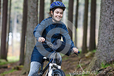 Teenage girl biking on forest trails