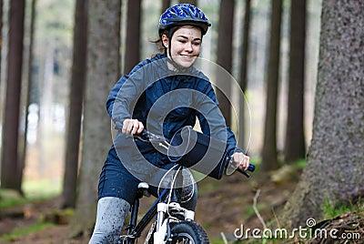 Teenage girl biking on forest trails