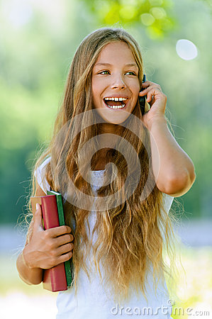 Teenage girl with books talking on