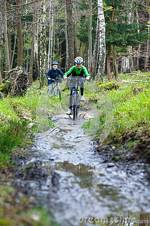 Teenage girl and boy biking on forest trails