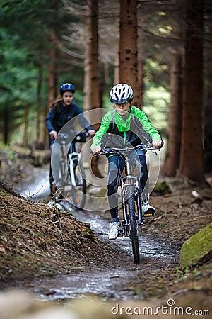 Teenage girl and boy biking on forest trails