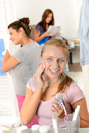 Teenage girl cleaning face with cotton pad