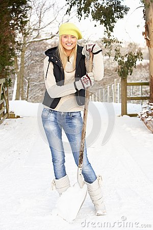 Teenage Girl Clearing Snow From Drive