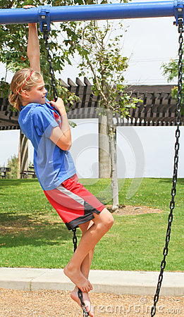 Teenage girl climbing swing chain