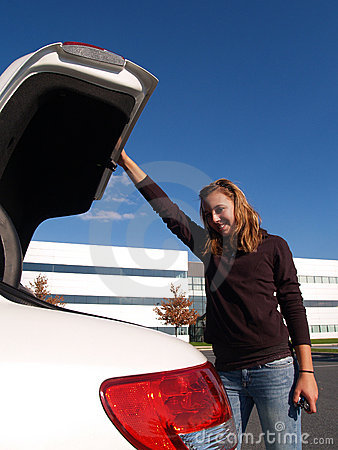 Teenage girl closing car trunk