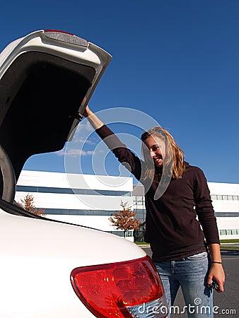 Teenage girl closing car trunk